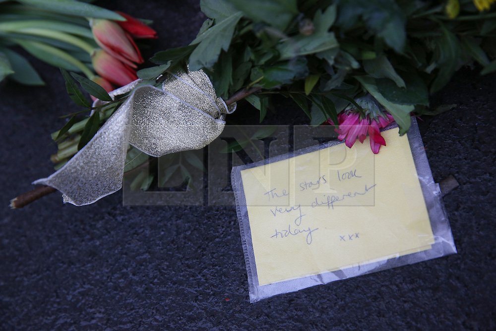 © Licensed to London News Pictures. 11/01/2016. London, UK. Flowers and song lyrics are placed at a mural of David Bowie in Brixton. The Death of David Bowie, who was born in Brixton, has been announced today.  Photo credit: Peter Macdiarmid/LNP