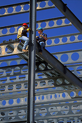 Stock photo of workers sitting high up on steel beams of a building that they are working on