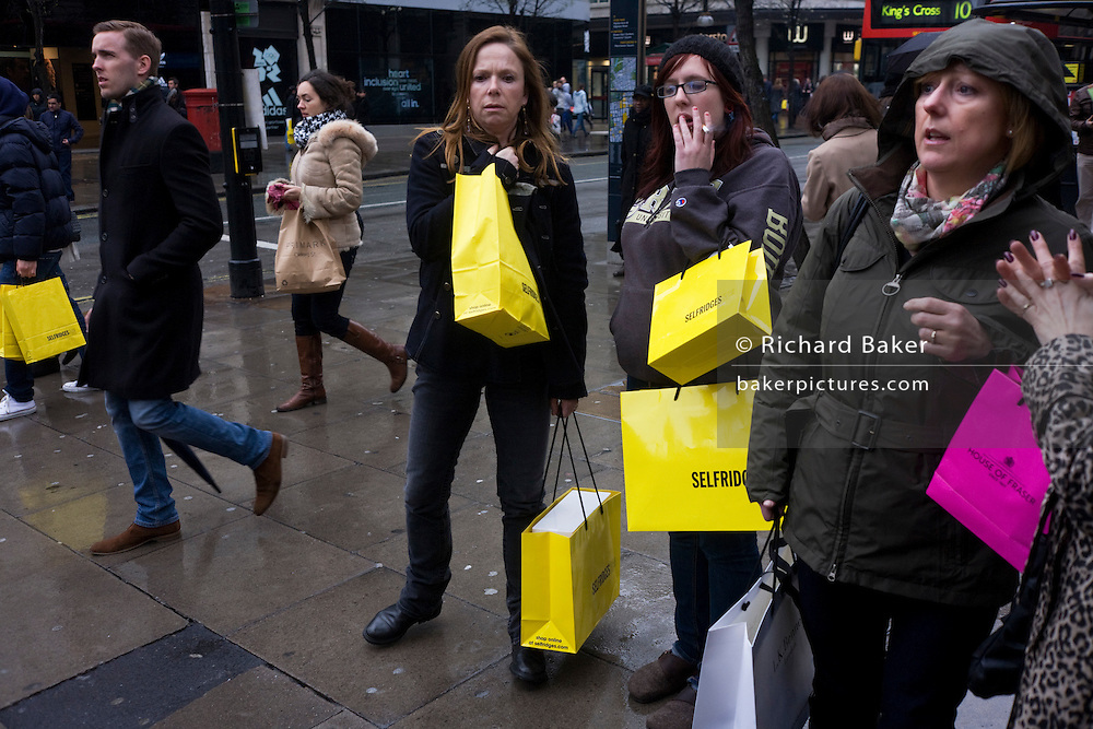 Women shoppers carry their purchases in yellow Selfridges bags in London's Oxford Street.