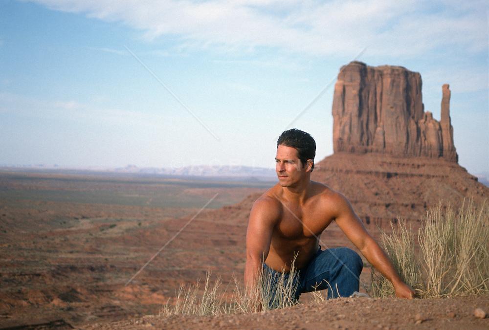 Man without a shirt climbing a  hillside in Monument Valley, AZ