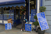As the second week of the Coronavirus lockdown continues around the capital, and the UK death toll rising by 563 to 2,325, with 800,000 reported cases of Covid-19 worldwide, a youth slips of protective gloves before entering a local butchers shop where only 2 customers at a time are being served and signs warn that social distancing must be observed according to government guidelines and restrictions, on 1st April 2020, in Clapham south London, England.