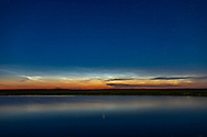 Noctilucent clouds (NLCs) low across the northern horizon with Capella just above the illuminated clouds and circumpolar from my latitude of 50&deg; North. <br /> <br /> This was June 24/25, 2018, just after midnight, from southern Alberta.<br /> <br /> This is a single exposure with the 35mm lens and Canon 6D MkII.
