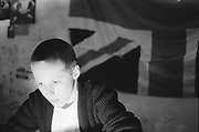 Young skinhead boy in front of Union Jack, UK, 1980s.