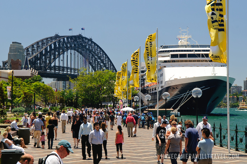 Tourists along the waterfront of Sydney's Circular Quay, with the Sydney Harbour Bridge in the background and a large cruise ship docked