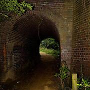 A dark pedestrian bypass under a deserted rural railroad line in Balby, Doncaster, England.