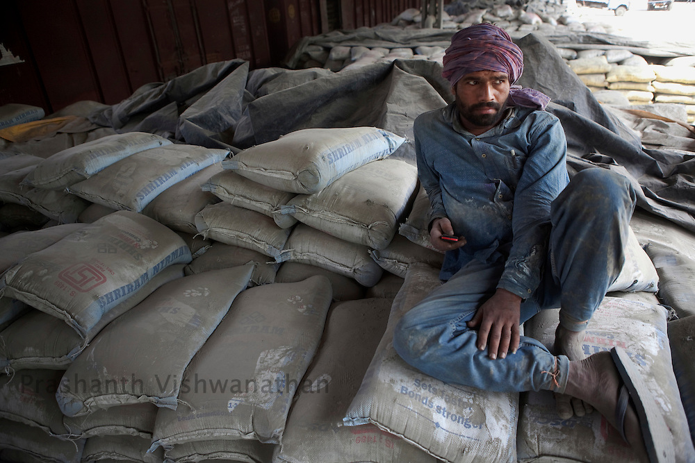A labourer rests on cement bags after unloading then manually from freight trains at the Shakur Basti station in New Delhi, India, on Tuesday April 5, 2011.  Photographer: Prashanth Vishwanathan/Bloomberg News