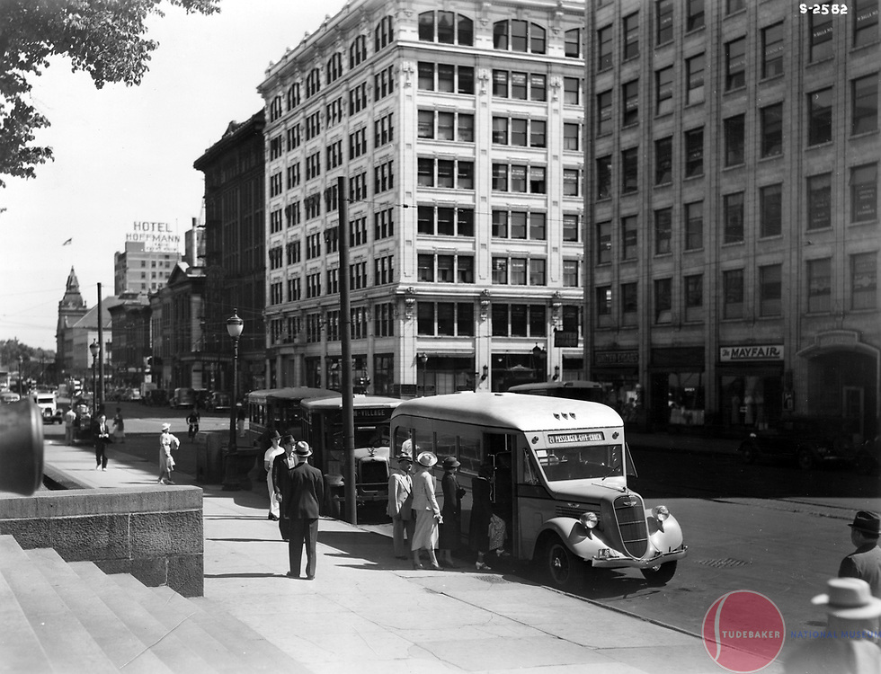 A 1936 Studebaker bus is pictured in downtown South Bend in front of the city's courthouse on Main Street.  The JMS Building shown in the large white building in the background.