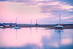 © Licensed to London News Pictures. 26/03/2018. Wells Next The Sea UK. Boats reflect into the harbour water at dawn this morning in Wells Next The Sea in Norfolk. Photo credit: Andrew McCaren/LNP