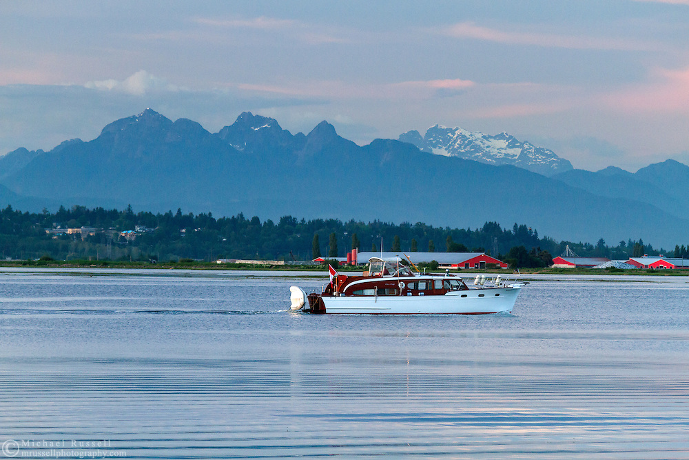 A yacht heading back to the Crescent Beach Yacht Club on the Nicomekle River at Blackie Spit in Surrey, British Columbia, Canada