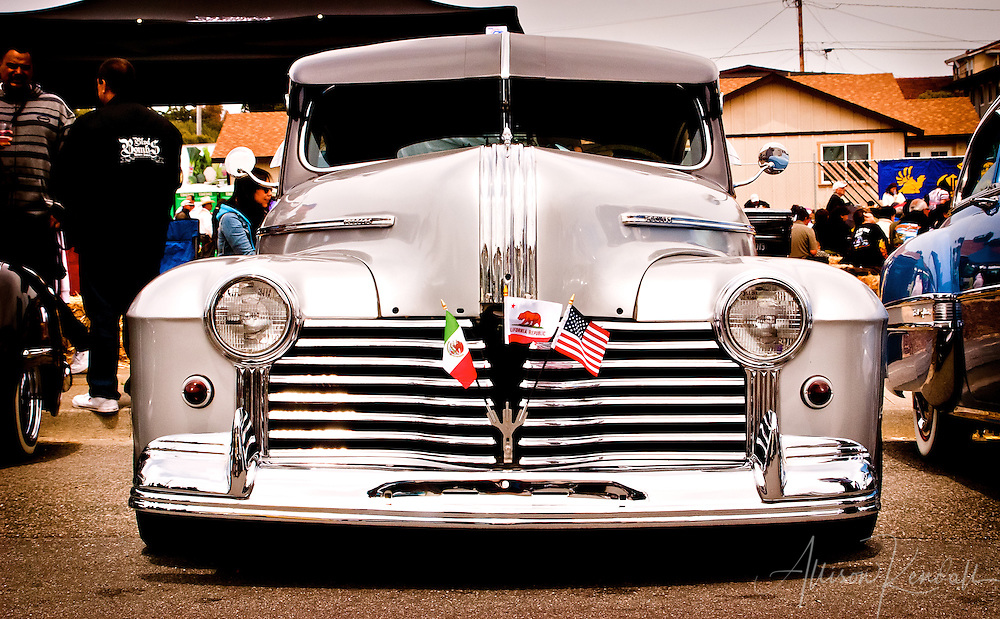 A hot rod custom classic automobile with a gleaming chrome grill shows the colors of the Mexican, Californian, and United States flags