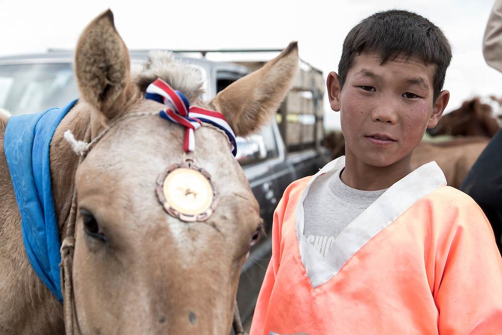 A young boy stands beside his winning horse displaying his medal on top of the horses nose after competing in the Naadam Festival at the Three Camel Lodge in the Gobi Desert of Mongolia on July 31, 2012. Horse racing is one of the ?Three Manly Sports? practiced during the Naadam Festival. © 2012 Tom Turner Photography