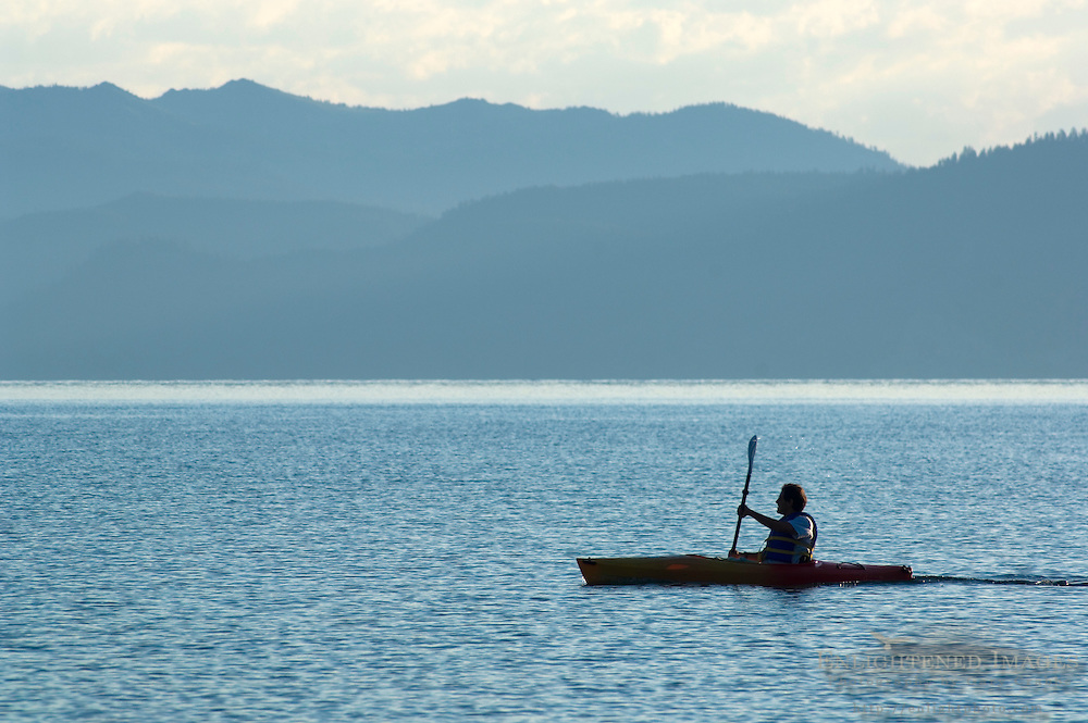 Kayaker paddle in kayak boat on calm blue water of Lake Tahoe, from Kiva Beach, California