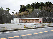 A roadside shop lies boarded up on the edge of the exclusion zone, near Namie, Japan. Some areas inside the exclusion zone and around may remain deserted forever.