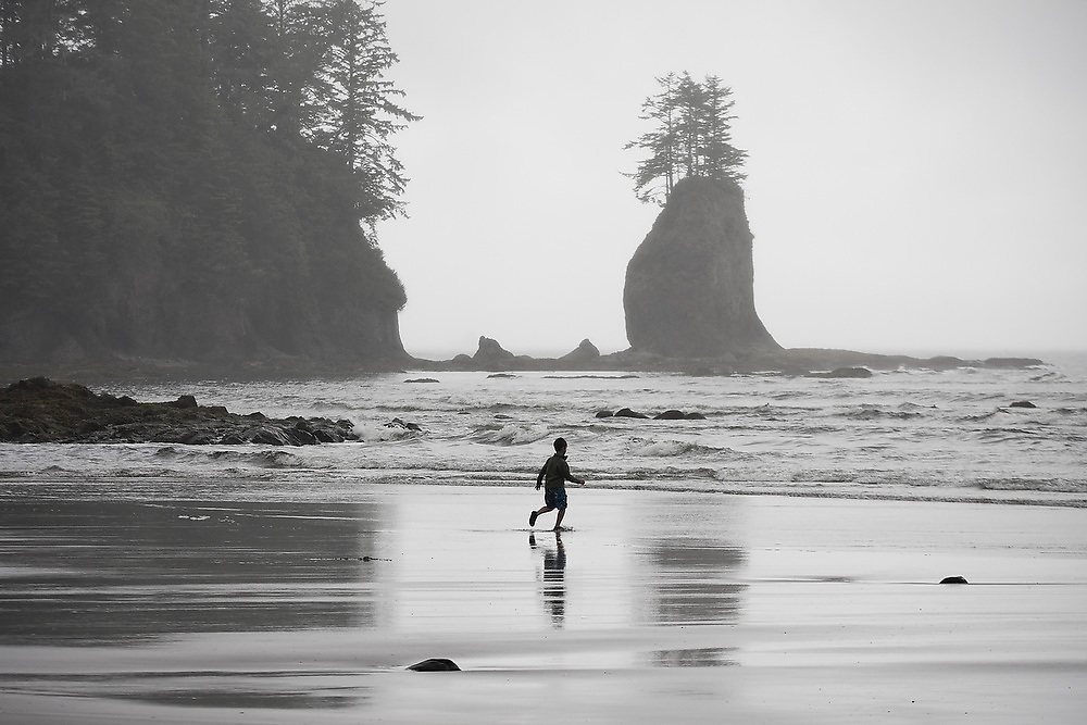 A young boy runs on the beach below a sea stack along the North Coast, Olympic National Park, Washington.