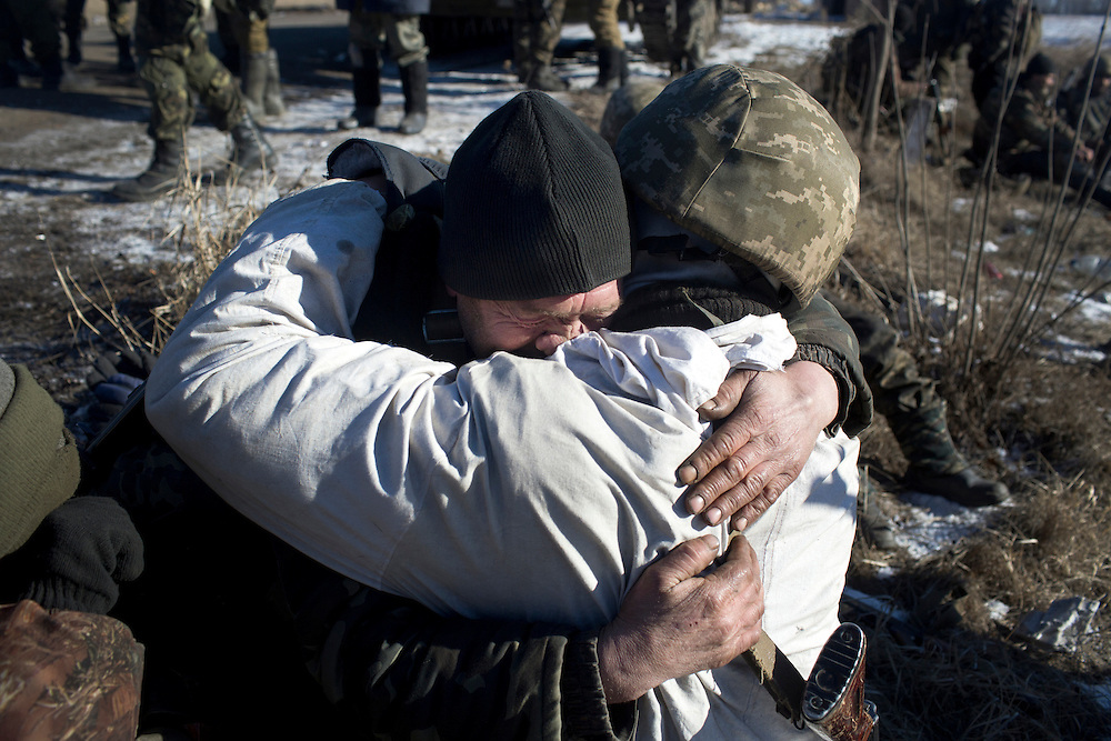 Soldiers embrace after being reunited at a crossroads on a road about 35 kilometers from Debaltseve, Ukraine February 18, 2015. The soldiers had withdrawn from Debaltseve earlier in the day and were regrouping at a crossroads before heading towards Artemivsk.
