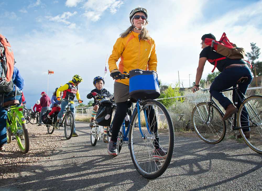 """mkb051917f/metro/Marla Brose --  Karla Koch, center, and her son Kadroma Saari, 4, head south on the North Diversion Channel Trail after stopping at a Bike to Work stop for coffee, snacks, trail maps and other swag, Friday, May 19, 2017.  Karla's husband Thondup Saari and their daughter  Tinle, 6, were right behind them. They were headed to the children's school before riding to work. """"We try to ride all the time,"""" Saari said.  At least 150 people visited the stop Friday morning, May 19, 2017. There were about 16 stops participating in Albuquerque and Rio Rancho. (Marla Brose/Albuquerque Journal)"""