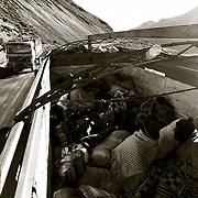 VIAJAR EN LAS CAJAS DE LOS CAMIONES ES MAS BARATO QUE LOS AUTOBUSES PERO AL MISMO TIEMPO MUCHO MAS INCOMODO POR EL FRIO Y LA LLUVIA ADEMAS DE PELIGROSO. CARRETERA DE LOS YUNGAS .BOLIVIA.<br /> FOTO . JORDI CAMI