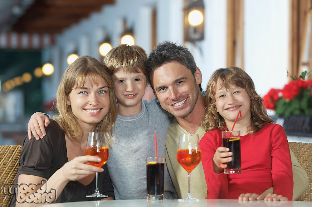 Parents and children (7-9) with drinks at restaurant portrait