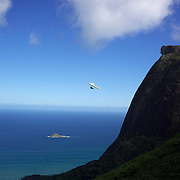 A tandem hang glider flies above the hillside of Pedro Bonita high in the hills of Rio de Janeiro. Pilots of hang gliders and para gliders take tourists for tandem flights with breathtaking views of the city before landing on Sao Conrado beach. Rio de Janeiro,  Brazil. 9th September 2010. Photo Tim Clayton