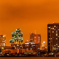 Panoramic picture of San Diego skyline at night with orange tone. San Diego is a major city in Southern California in the United States. Panoramic photo ratio is 1:3.