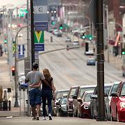 Couple on the sidewalk walking up Grand Avenue, Kansas City, MO.