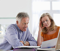 Senior couple looking at bills sitting at dining table