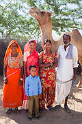 Nitu and Suki (in pink) (not their real names), stand with their parents and Suki's son in Jhaju village, Bikaner, Rajasthan, India on 4th October 2012. Now 18, Nitu was married off at age 10 to a boy of around the same age, but only went to live with her in-laws when she was 12, after she had finished studying up to class 6. The three sisters, aged 10, 12, and 15 were married off on the same day by their maternal grandfather while their father was hospitalized. She was abused by her young husband and in-laws so her father took her back after hearing that her husband, who works in a brick kiln, was an alcoholic and was doing drugs and crime. She had only spent a few days at her husband's house at that time. Her father (now out of the hospital) has said that she will only be allowed to return to her husband's house if he changes his ways but so far, the negotiations are still underway. Her sister, Suki, now age 20, was married off at age 12 but only went to live with her husband when she was 14. Her husband died three years after she moved in, leaving her with a daughter, now 6, and a son, now 4. She has no parents-in-laws and thus returned to her parents house after being widowed because her brother-in-law, who had become the head of the family after his brother's death, had refused to allow Suki to inherit her deceased husband's fair share of agriculture land. Although Suki's father wants her to remarry, she refuses to, hoping instead to be able to support her family through embroidery and tailoring work. The family also makes hand-loom cotton to subsidize their collective household income. Photo by Suzanne Lee for PLAN UK