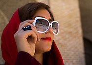 Iran, Bisotun, Iranian woman wearing sunglasses. In the urban areas, women wear brightly colored scarves pushed back to expose plenty of hair. Sunglasses are also a way to express individuality.