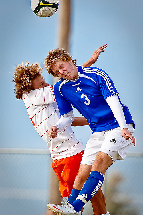 JEROME A. POLLOS/Press..Coeur d'Alene High's Casey Shellman goes up for a header against Nathan White from Post Falls High during Saturday's 5A Region 1 tournament championship game. The Vikings beat the Trojans 1-0 in Post Falls.