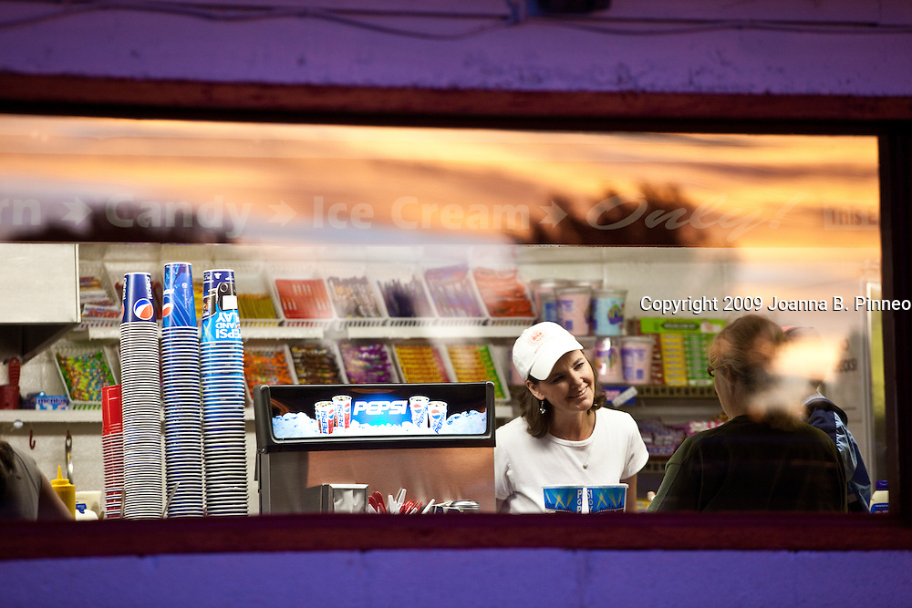 Glenda Field, a long time employee at the Star Drive-in serves a customer at the concession stand as the sun sets. Montrose, Colorado