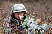 Apr, 9, 2011, Camp Edwards, Massachusetts - Cadet Jon Broderick lies prone in the brush during the ROTC Spring Field Training. As part of the training cadets are assessed on their qualities as leaders.