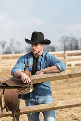 sexy cowboy with a saddle over his shoulder on a ranch All American cowboy on a ranch