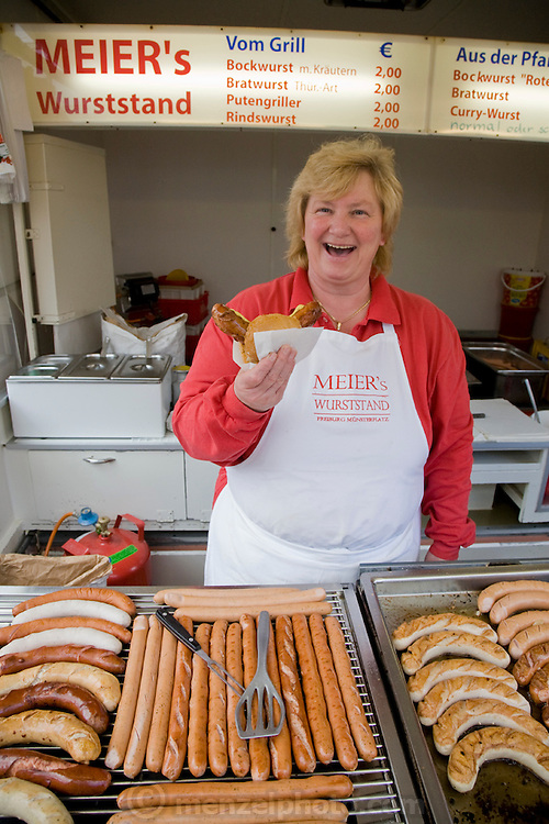 A woman sells wursts at a stand in the central square at  Munsterplatz in Freiburg im Breisgau, Germany.