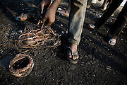 A boy handles a bundle of copper wire after burning off the plastic that covered it near the Agbogboloshie market in Accra, Ghana on Thursday August 21, 2008..