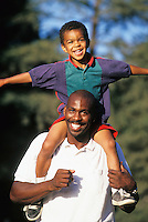 Mid 30's African American father with his mixed race son on his shoulders.<br />