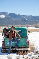 hot rugged cowboy leaning against a rustic truck in the snow