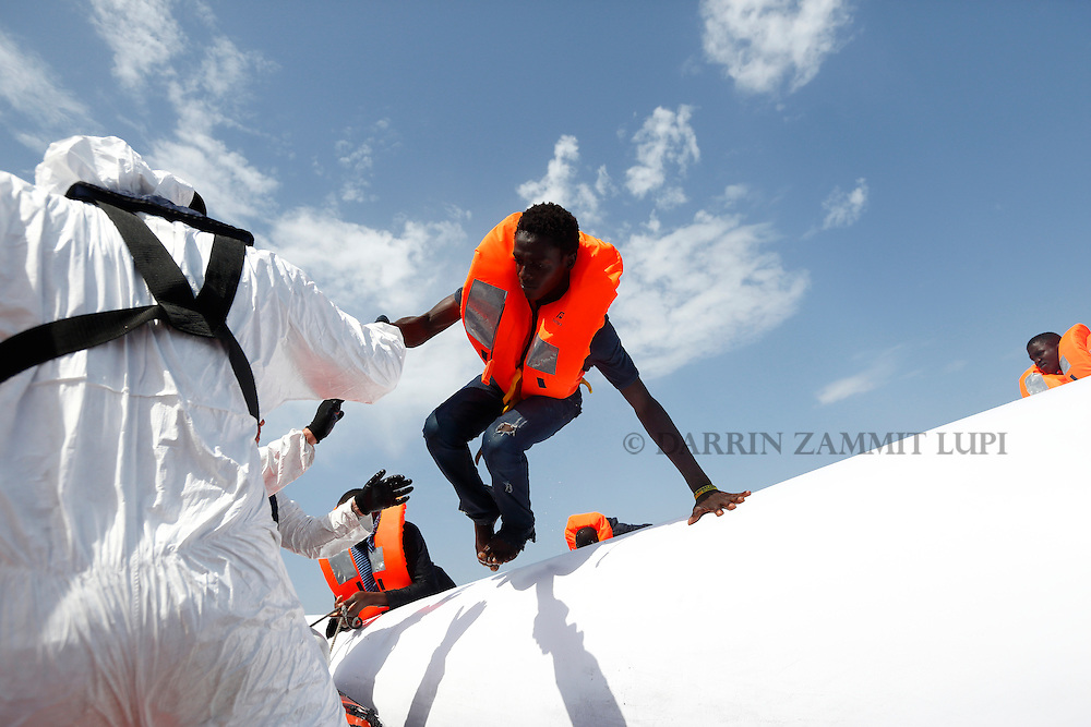 A migrant jumps from a rubber dinghy to a Migrant Offshore Aid Station (MOAS) RHIB (Rigid-hulled inflatable boat) before being taken to the MOAS ship MV Phoenix some 20 miles (32 kilometres) off the coast of Libya, August 3, 2015.  118 migrants were rescued from a rubber dinghy off Libya on Monday morning . The Phoenix, manned by personnel from international non-governmental organisations Medecins san Frontiere (MSF) and MOAS, is the first privately funded vessel to operate in the Mediterranean.<br /> REUTERS/Darrin Zammit Lupi <br /> MALTA OUT. NO COMMERCIAL OR EDITORIAL SALES IN MALTA