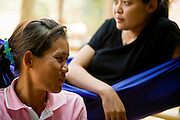 18 FEBRUARY 2008 -- BONG TI, KANCHANABURI, THAILAND: Women relax and chat at the Bamboo School in Bong Ti, Thailand, about 40 miles from the provincial capital of Kanchanaburi. Sixty three children, most members of the Karen hilltribe, a persecuted ethnic minority in Burma, live at the school under the care of Catherine Riley-Bryan, whom the locals call MomoCat (Momo is the Karen hilltribe word for mother). She provides housing, food and medical care for the kids and helps them get enrolled in nearby Thai public schools. Her compound is about a half mile from the Thai-Burma border. She also helps nearby Karen refugee villages by digging water wells for them and providing medical care.  Photo by Jack Kurtz