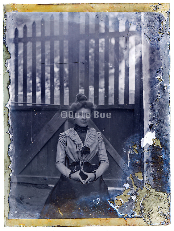 vintage portrait of adult woman sitting with a gate in the background early 1900s