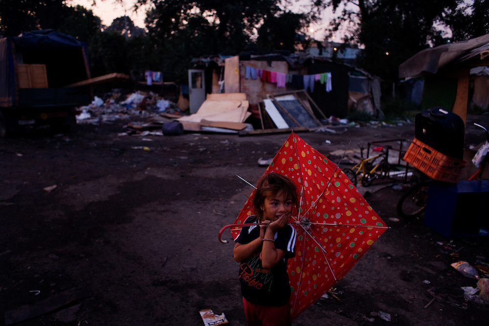 The last night of the Gazela settlements, families making final preparations for the following day's move. Girl with an umbrella.