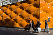 Muslim shoppers walk past the temporary renovation hoarding of luxury brand Louis Vuitton in New Bond Street, on 27th February 2019, in London, England.