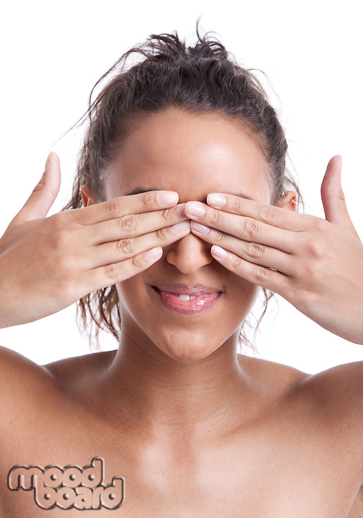 Young Mixed Race woman covering her eyes with hands against white background