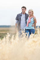 Portrait of young couple standing at field