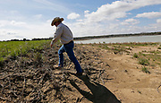 Mike Dee, owner of Dee River Ranch in western Pickens County, shows the drought impact on his farm operation Friday, March 10, 2017.  Dee climbs the bank of a reservoir he uses to irrigate his row crops. The reservoir is still down ten feet and has been down by as much as twenty feet. The reservoir encompasses between 100 and 110 acres when filled to capacity.  [Staff Photo/Gary Cosby Jr.]