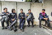 07 AUGUST 2013 - BANGKOK, THAILAND: Women Thai riot police relax after working a checkpoint to prevent Thai protesters from getting to the Parliament building. About 2,500 protestors opposed to an amnesty bill proposed by Thailand's ruling party marched towards the Thai parliament in the morning. The amnesty could allow exiled fugitive former Prime Minister Thaksin Shinawatra to return to Thailand. Thaksin's supporters are in favor of the bill but Thai Yellow Shirts and government opponents are against the bill. Thai police deployed about more than 10,000 riot police and closed roads around the parliament. Although protest leaders called off the protest rather than confront police, a few people were arrested for assaulting police when they tried to break through police lines. Several police officers left the scene under medical care after they collapsed in the heat.     PHOTO BY JACK KURTZ