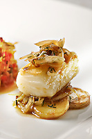 Fried cod over a bed of sliced potatoes, caramelized onion on top, A classic spanish dish and tapa from the basque region
