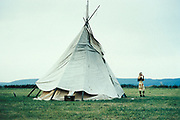 A woman stood outside a teepee in a field. Hostomice Techno Festival. Czech Republic 1996