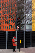 Woman wearing matching red beret and coat stands beneath orange and yellow architecture.