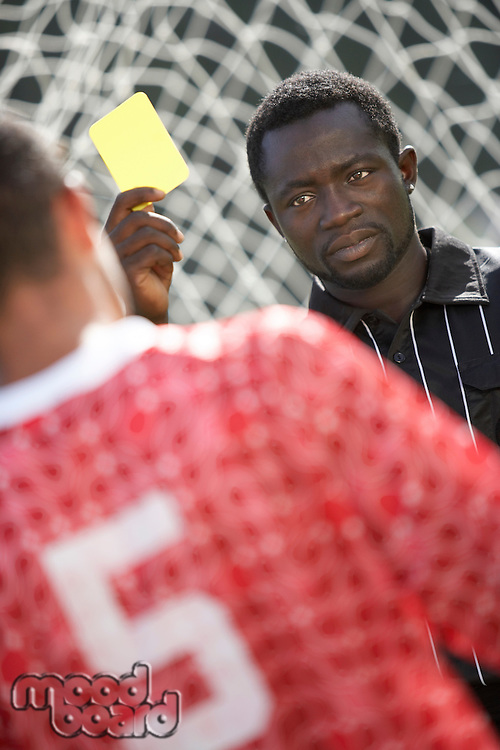 Soccer Referee Holding Out a Yellow Card