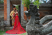 A couple poses in traditional Balinese wedding attire in the Bali Museum located in the city of Denpasar, Bali, Indonesia.